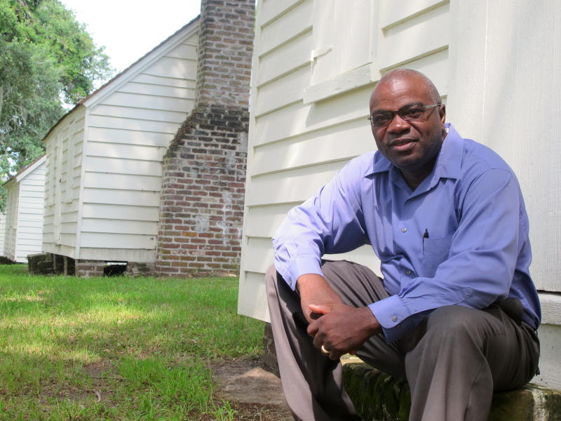 In this Aug. 14, 2013 photo. Joe McGill, who works with the National Trust For Historic Preservation, sits outside one of the slave cabins at McLeod Plantation in Charleston, S.C. As part of the Slave Dwelling Project, McGill has slept in old slave dwellings in a dozen states during the past three years to draw attention to the need to preserve the structures and tell their stories.(AP Photo/Bruce Smith, File)