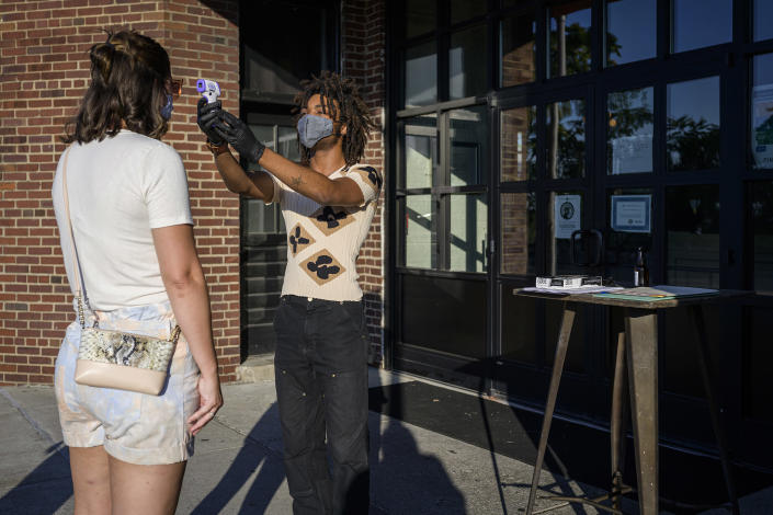 A Pinewood Social host conducts a temperature check of a patron in Nashville, Tenn., on Aug. 7, 2020. (William DeShazer/The New York Times)