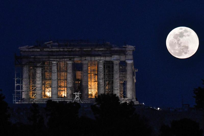The supermoon rises next to the Parthenon Temple at the Acropolis archaeological site on Tuesday.