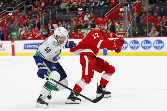 Vancouver Canucks center Tim Schaller (59) holds Detroit Red Wings defenseman Filip Hronek (17) while chasing the puck during the third period of an NHL hockey game Tuesday, Oct. 22, 2019, in Detroit. (AP Photo/Paul Sancya)