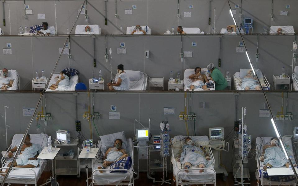 """<span class=""""caption"""">A field hospital in São Paulo state, Brazil, on March 26, 2021. Brazil keeps setting new COVID-19 records, with up to 4,000 people dying daily. </span> <span class=""""attribution""""><a class=""""link rapid-noclick-resp"""" href=""""https://www.gettyimages.com/detail/news-photo/patients-affected-by-the-covid-19-coronavirus-remain-at-a-news-photo/1231952275?adppopup=true"""" rel=""""nofollow noopener"""" target=""""_blank"""" data-ylk=""""slk:Miguel Schincariol/AFP via Getty Images"""">Miguel Schincariol/AFP via Getty Images</a></span>"""