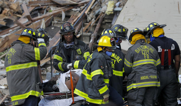 Baltimore City Fire Department carries a person out from the debris after an explosion in Baltimore on Monday, Aug. 10, 2020. / Credit: Julio Cortez / AP