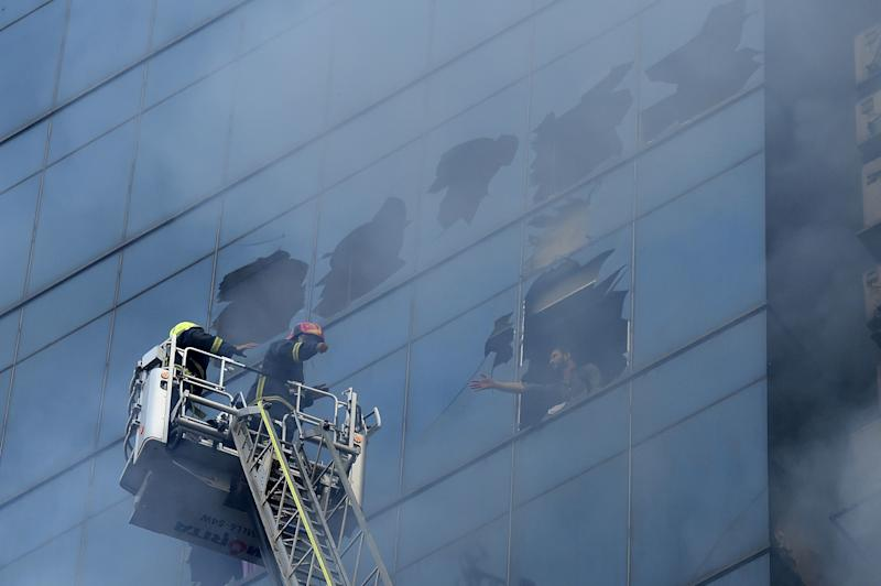 A man trapped inside a burning office building gestures at Bangladeshi firefighters for help in Dhaka on March 28, 2019. (Photo: Munir Uz Zaman/AFP/Getty Images)