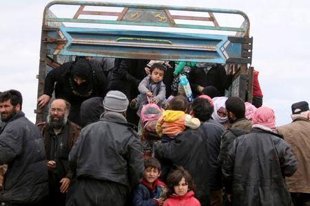 Internally displaced Syrian people who fled Raqqa city get out of a truck at a camp in Ain Issa