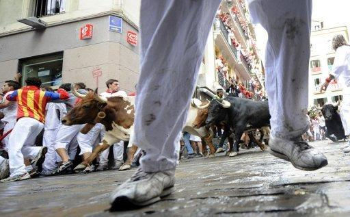 Participants run in front of Dolores Ybarra's bulls during the bull run of the San Fermin Festival in Pamplona, northern Spain. An elderly man was gored and five other people hurt as daredevils fled half-tonne bulls thundering through the streets Saturday in the first bull run of Spain's San Fermin festival