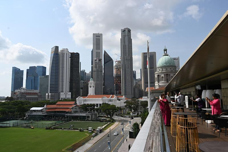Singapore's city skyline is seen as visitors take photographs from the rooftop bar of the National Gallery on January 13, 2020. (Photo by Roslan RAHMAN / AFP) (Photo by ROSLAN RAHMAN/AFP via Getty Images)