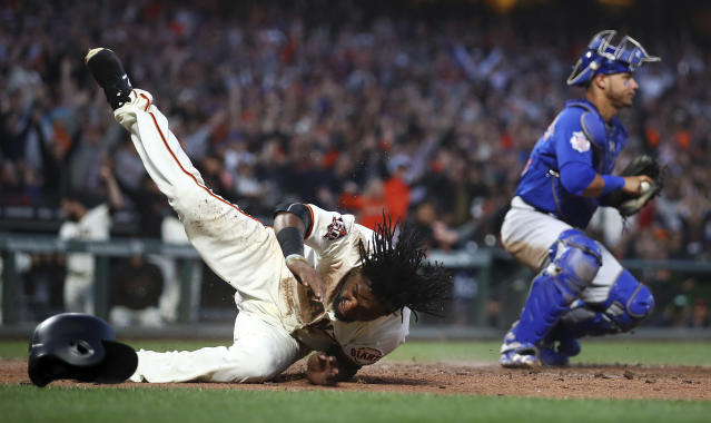 San Francisco Giants' Alen Hanson, left, tumbles after scoring against Chicago Cubs catcher Willson Contreras in the fifth inning of a baseball game Monday, July 9, 2018, in San Francisco. (AP Photo/Ben Margot)