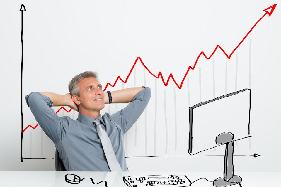 A relaxed man sitting at a desk with a red arrow that's increasing on a chart behind him.