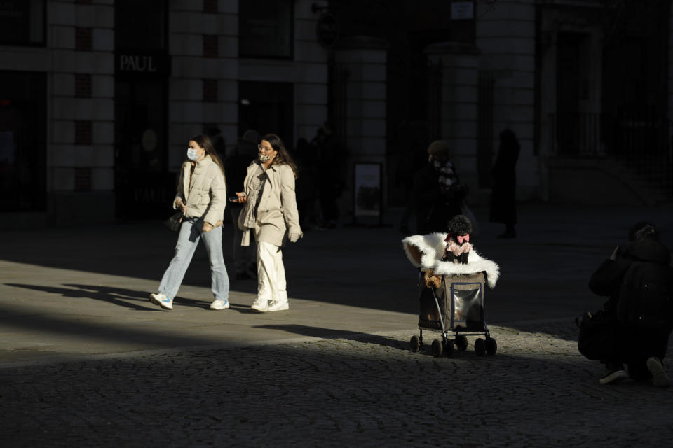 A person photographs their dog near St Paul's Cathedral in the City of London financial district of London, Friday, Jan. 22, 2021, during England's third national lockdown since the coronavirus outbreak began. The U.K. is under an indefinite national lockdown to curb the spread of the new variant, with nonessential shops, gyms and hairdressers closed, most people working from home and schools largely offering remote learning. (AP Photo/Matt Dunham)