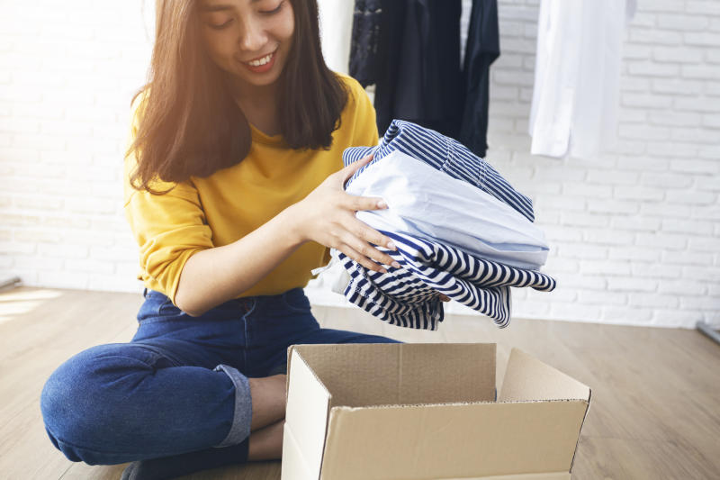 A young woman removes clothes from a cardboard box.