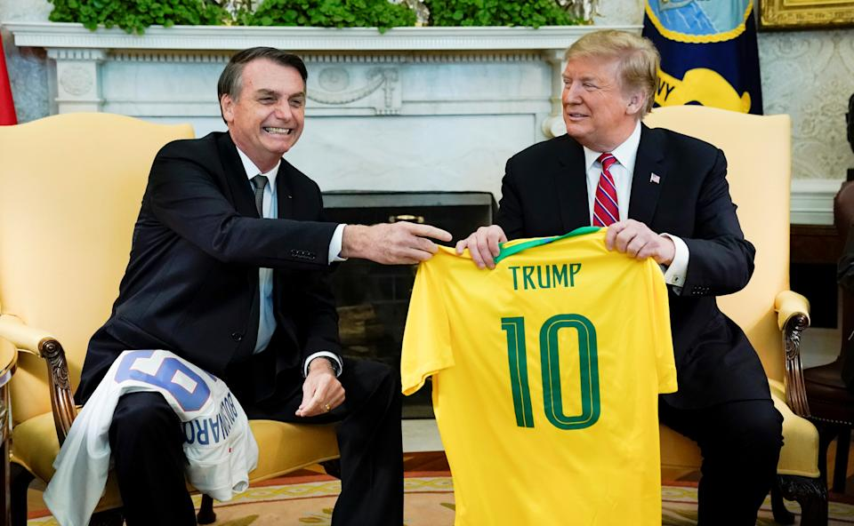 Brazil's President Jair Bolsonaro presents a Brazil naitonal soccer team jersey to U.S. President Donald Trump after Trump gave him a U.S. soccer team jersey during a meeting in the Oval Office of the White House in Washington, U.S., March 19, 2019. REUTERS/Kevin Lamarque