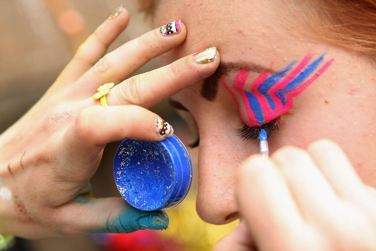 "BERLIN, GERMANY - JULY 21:  An attendee gets her face painted with glitter at the second annual Hipster Olympics on July 21, 2012 in Berlin, Germany. With events such as the ""Horn-Rimmed Glasses Throw,"" ""Skinny Jeans Tug-O-War,"" ""Vinyl Record Spinning Contest"" and ""Cloth Tote Sack Race,"" the Hipster Olympics both mocks and celebrates the Hipster subculture, which some critics claim could never be accurately defined and others that it never existed in the first place. The imprecise nature of determining what makes one a member means that the symptomatic elements of adherants to the group vary in each country, but the archetype of the version in Berlin, one of the more popular locations for those following its lifestyle, along with London and Brooklyn, includes a penchant for canvas tote bags, the carbonated yerba mate drink Club Mate, analogue film cameras, an asymetrical haircut, 80s neon fashion, and, allegedly, a heavy dose of irony. To some in Berlin, members of the hipster ""movement"" have replaced a former unwanted identity in gentrifying neighborhoods, the Yuppie, for targets of criticism, as landlords raise rents in the areas to which they relocate, particularly the up-and-coming neighborhood of Neukoelln.  (Photo by Adam Berry/Getty Images)"