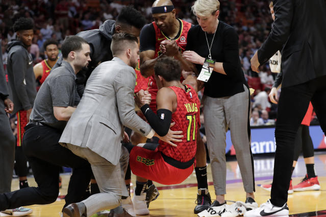Atlanta Hawks guard Trae Young was helped off the court after rolling his ankle Tuesday night in Miami. (Lynne Sladky/AP)