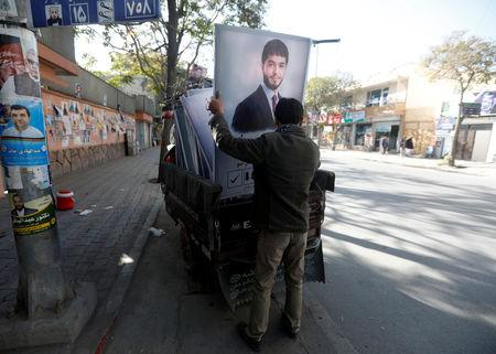 An Afghan man prepares posters of a parliamentary election candidate ahead of the elections in Kabul, Afghanistan October 18, 2018. REUTERS/Omar Sobhani