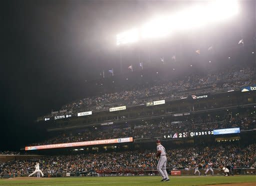 San Francisco Giants starting pitcher Tim Lincecum, left, throws to Arizona Diamondbacks' Jason Kubel as fog rolls in during the first inning of a baseball game Tuesday, Sept. 25, 2012, in San Francisco. (AP Photo/Marcio Jose Sanchez)