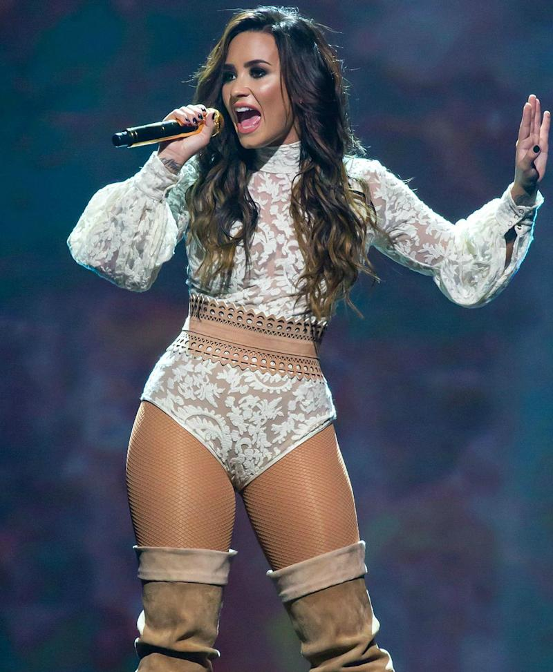During a stage performance, Demi Lovato sports a see-through low-cut outfit with knee-high boots to match