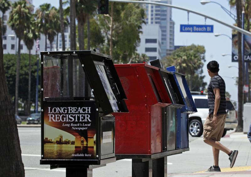 This Aug. 15, 2013, photo shows new, empty news stands ready to hold copies of the Long Beach Register on Ocean Boulevard in Long Beach, Calif. Published by the Orange County Register, the Long Beach Register makes its five-day-a-week debut Monday, Aug. 19. It's the first expansion of the Register outside of Orange County under new owners Aaron Kushner and Eric Spitz, who bought the newspaper's parent company, Freedom Communications Inc., last year. The Long Beach Register will have a newsroom staff of 20 and compete with the established newspaper in town, the Long Beach Press-Telegram. (AP Photo/Reed Saxon)