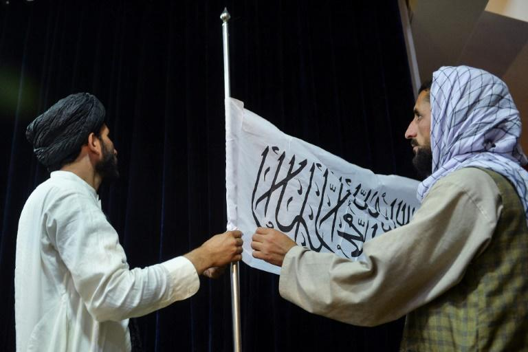 Cadres adjust the Taliban flag ahead of a press conference by its chief spokesman in Kabul