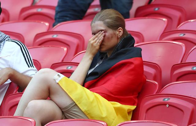 <p>Germany fans look dejected after the match as they go out of the World Cup. REUTERS/Pilar Olivares </p>