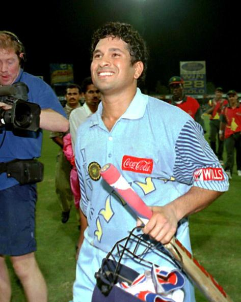 SHARJAH, UNITED ARAB EMIRATES:  India's Sachin Tendulkar enjoys a moment of glory after leading  his team to victory at the  Coca Cola Trophy in Sharjah 13 November. India beat Zimbabwe by 10 wickets in the final of the week-long tournament. World champions Sri Lanka failed to register a single victory. Tendulkar scored a century with 6 sixes in today's match and was named man-of-the-tournament. (Photo credit should read JORGE FERRARI/AFP/Getty Images)