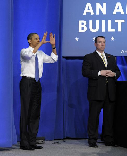 President Barack Obama does the signature University of Miami hand gesture as he prepares to speak at the University of Miami in Coral Gables, Thursday, Feb. 23, 2012. (AP Photo/Susan Walsh)