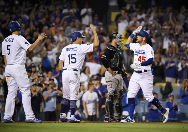 Los Angeles Dodgers' Matt Beaty, right, is congratulated by Corey Seager, left, and Austin Barnes, second from left, as Miami Marlins catcher Bryan Holaday stands at the plate during the eighth inning of a baseball game Saturday, July 20, 2019, in Los Angeles. (AP Photo/Mark J. Terrill)