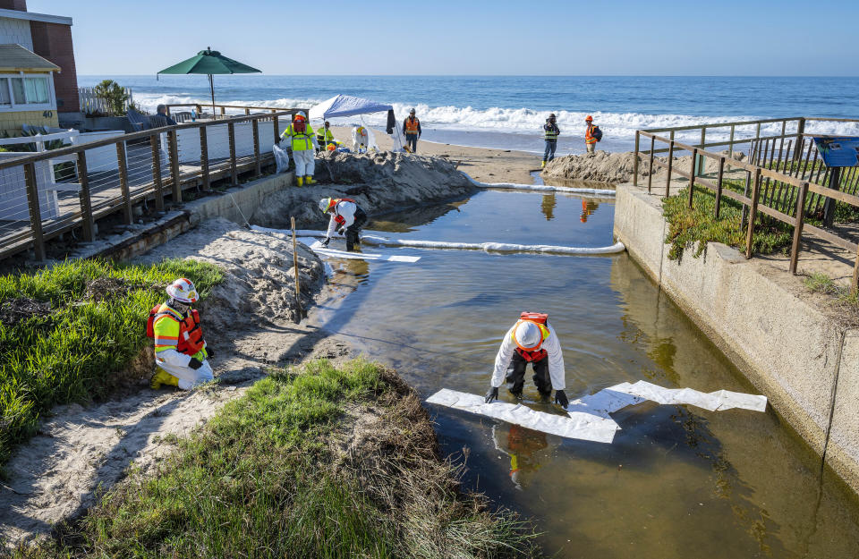 Shoreline cleanup crews use absorbent material to soak up any oil that may have made its way into a small creek that flows into the ocean at Crystal Cove State Park in Laguna Beach, Calif., Thursday, Oct. 14, 2021. Shoreline cleanup crews continue to pick up tar balls that have washed ashore onto the sand, rocks and vegetation, remnants of the offshore oil spill near Huntington Beach in early October. (Mark Rightmire/The Orange County Register via AP)