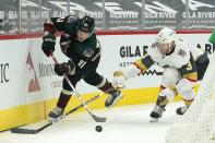 Arizona Coyotes center Drake Caggiula (91) passes the puck in front of Vegas Golden Knights defenseman Brayden McNabb (3) during the first period of an NHL hockey game Friday, Jan. 22, 2021, in Glendale, Ariz. (AP Photo/Ross D. Franklin)