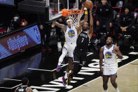 Brooklyn Nets forward Kevin Durant (7) shoots as Golden State Warriors forward Kelly Oubre Jr. (12) defends with Golden State Warriors forward Eric Paschall (7) looking on from the floor during the first quarter of an opening night NBA basketball game, Tuesday, Dec. 22, 2020, in New York. (AP Photo/Kathy Willens)