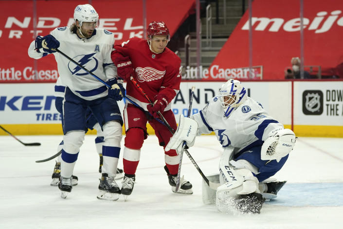 Tampa Bay Lightning goaltender Curtis McElhinney (35) stops a shot as Detroit Red Wings center Vladislav Namestnikov (92) watches for a rebound as Victor Hedman (77) defends in the second period of an NHL hockey game Saturday, May 1, 2021, in Detroit. (AP Photo/Paul Sancya)