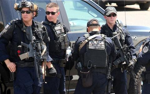 U.S. Customs and Border Protection officers gather near the scene of a shooting at a shopping mall in El Paso - Credit: AP