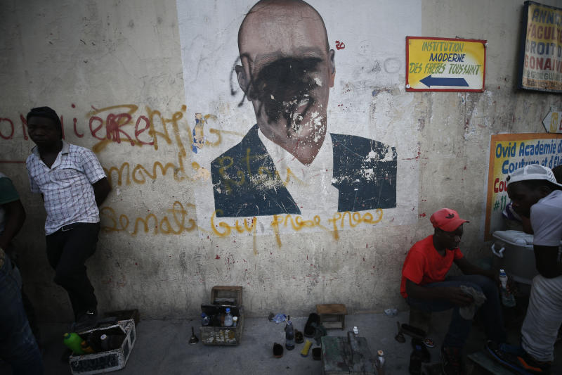 A man shines a client's shoes as another waits for business, in front of a wall painted with an image of President Jovenel Moise, his face obscured by black spray paint, in the Delmas neighborhood of Port-au-Prince, Haiti, Tuesday, Oct. 8, 2019. The country has entered its fourth week of anti-government protests that have paralyzed the economy and shuttered schools as demonstrators demand the resignation of the president. (AP Photo/Rebecca Blackwell)
