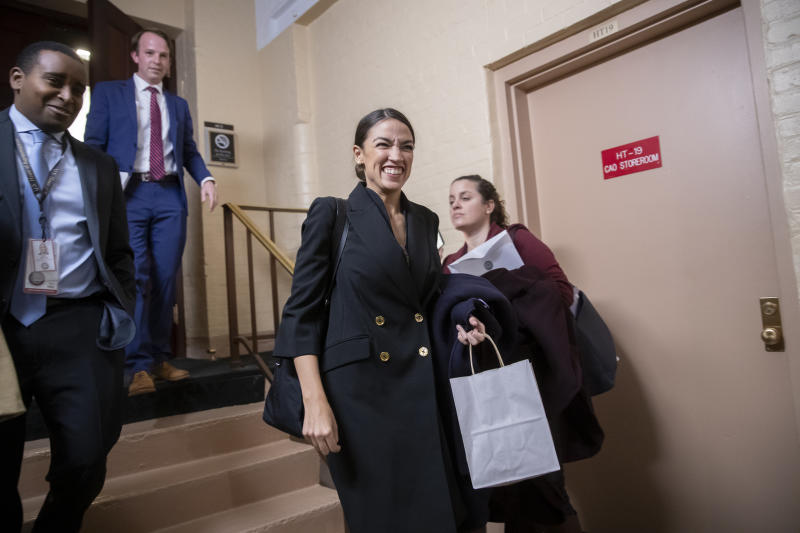 FILE - In this Nov. 15, 2018, file photo, Rep.-elect Alexandria Ocasio-Cortez, D-N.Y., joined at left by Rep.-elect Joe Neguse, D-Colo., exit a Democratic Caucus meeting in the basement of the Capitol in Washington. Ocasio-Cortez seems to be everywhere. She's cooked soup, live on Instagram. She's done laundry in public. And she's clapped back at critics of her clothing and a misstatement. The New York Democrat, who at 29 is the youngest woman to be elected to Congress, says she's documenting her journey to Capitol Hill to lift some of the mystery of the place and make it, 'real.' (AP Photo/J. Scott Applewhite, File)