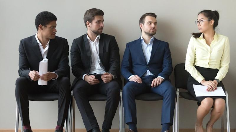 Diverse male applicants looking at female rival among men waiting for at job interview,