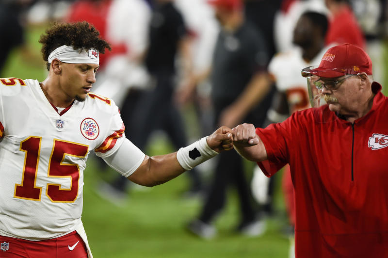 Chiefs quarterback Patrick Mahomes and head coach Andy Reid bump fists.