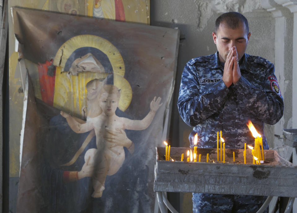 A policeman prays in the Holy Savior Cathedral, damaged by shelling by Azerbaijan's artillery during a military conflict in Shushi, the separatist region of Nagorno-Karabakh, Saturday, Oct. 24, 2020, with a damaged icon of the Virgin on the left. The heavy shelling forced residents of Stepanakert, the regional capital of Nagorno-Karabakh, into shelters, as emergency teams rushed to extinguish fires. Nagorno-Karabakh authorities said other towns in the region were also targeted by Azerbaijani artillery fire. (AP Photo)