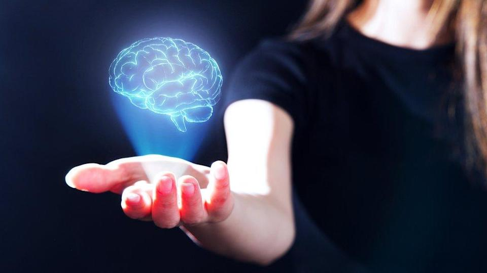 Concept image: A woman with the hologram of a brain projected on the palm of her hand