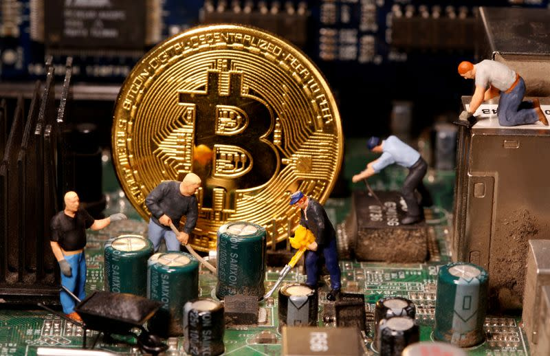 FILE PHOTO: A representation of virtual currency Bitcoin and small toy figures are placed on computer motherboard