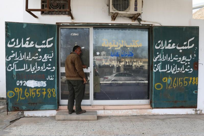 A man walks next to a real estate office in Tripoli
