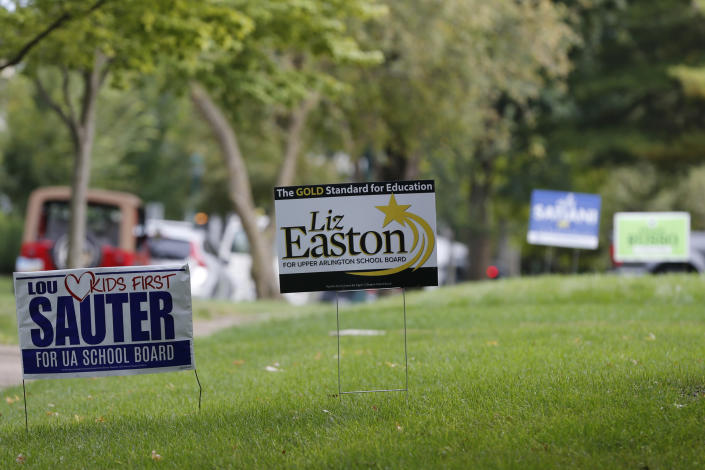 Campaign yard signs line a street Thursday, Oct. 7, 2021, in Upper Arlington, Ohio. Across Ohio and the nation, parental protests over social issues like mask mandates, gender-neutral bathrooms, teachings on racial history, sexuality and mental and emotional health are being leveraged into school board takeover campaigns. (AP Photo/Jay LaPrete)