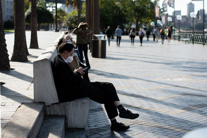 A man wears his mask while on his phone on a chair in front of First Fleet Park.