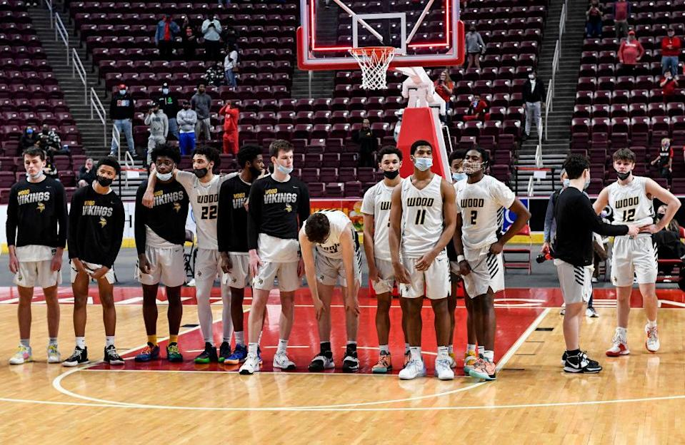 A multi-racial modern team stands on the court together