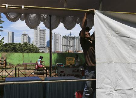 A volunteer makes preparations at a polling station for the upcoming parliamentary election in Jakarta April 8, 2014. REUTERS/Beawiharta