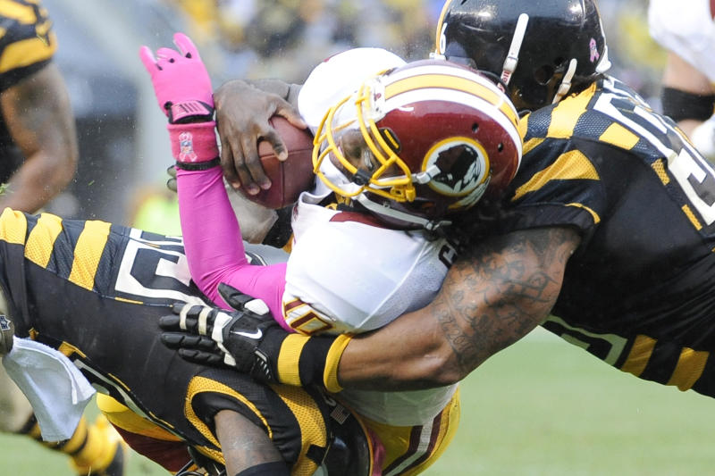 Washington Redskins quarterback Robert Griffin III, center, is stopped by Pittsburgh Steelers nose tackle Casey Hampton, right, and cornerback Keenan Lewis (23) in the second quarter during an NFL football game on Sunday, Oct. 28, 2012, in Pittsburgh. (AP Photo/Don Wright)