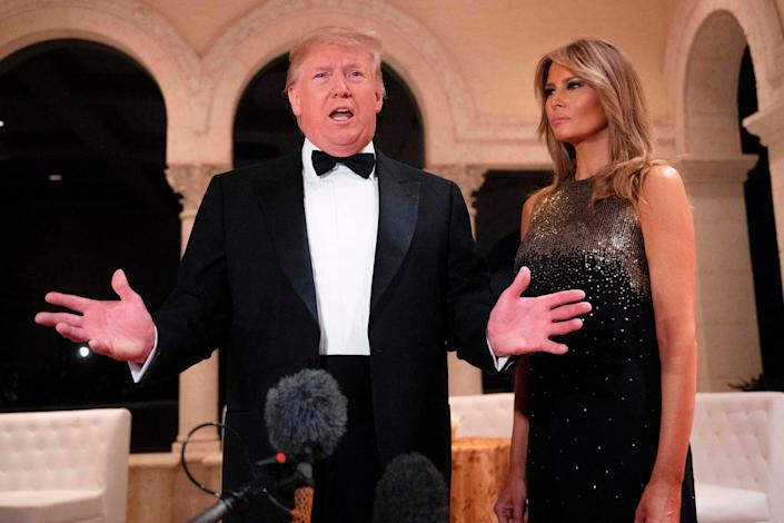 In this file photo taken on December 31, 2019, US President Donald Trump and First Lady Melania Trump speak to the press outside the grand ballroom as they arrive for a New Year's celebration at Mar-a-Lago in Palm Beach, Florida. - Trump's re-election team on January 2, 2020, revealed that he sits atop a staggering campaign war chest, underlining the scale of the challenge facing the US president's Democratic rivals at the start of an election year. In the fourth quarter of 2019, even as Trump was mired in a political scandal that resulted in his impeachment by the House of Representatives, he came out on top, raising a staggering $46 million. (Photo by JIM WATSON / AFP) (Photo by JIM WATSON/AFP via Getty Images) (AFP via Getty Images)