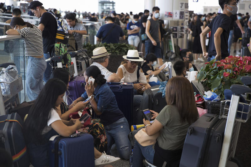Stranded travelers wait in the departure hall of the Hong Kong International Airport in Hong Kong, Tuesday, Aug. 13, 2019. (Photo: Vincent Thian/AP)