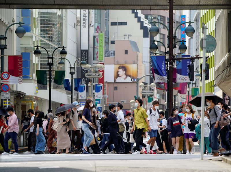 Passersby wearing protective face masks walk under the street decoration of Tokyo 2020 Olympic and Paralympic Games in Tokyo