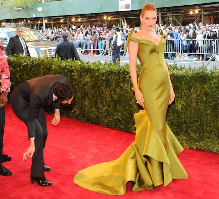 """Designer Zac Posen, left, fixes the dress of actress Uma Thurman as they attend The Metropolitan Museum of Art's Costume Institute benefit celebrating """"PUNK: Chaos to Couture"""" on Monday, May 6, 2013 in New York. (Photo by Evan Agostini/Invision/AP)"""