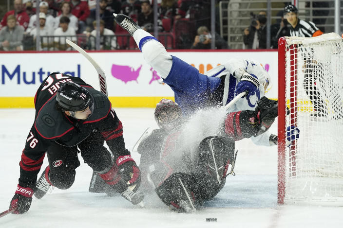 Tampa Bay Lightning center Anthony Cirelli, top right, falls over Carolina Hurricanes goaltender Alex Nedeljkovic, bottom right, while Hurricanes defenseman Brady Skjei (76) defends during the first period in Game 1 of an NHL hockey Stanley Cup second-round playoff series in Raleigh, N.C., Sunday, May 30, 2021. (AP Photo/Gerry Broome)