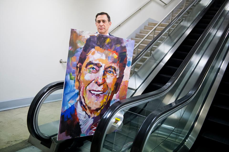 Rep. Darrell Issa (R-Calif.) walks through the basement of the Capitol with a painting of former President Ronald Reagan by artist Steve Penley on Feb. 11, 2015. The painting will be added to Issa's collection of Reagan memorabilia.